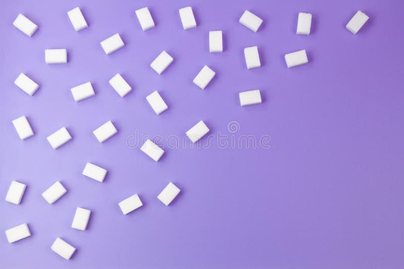 Würfel des raffinierten Zuckers vereinbarten in den diagonalen Linien auf purpurrotem Hintergrund stockfoto