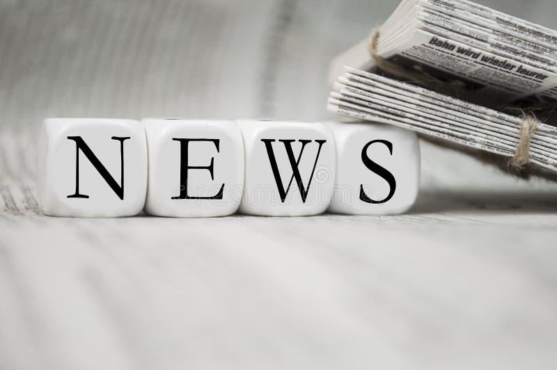 Würfel mit Nachrichten mit Zeitungen stockfotografie
