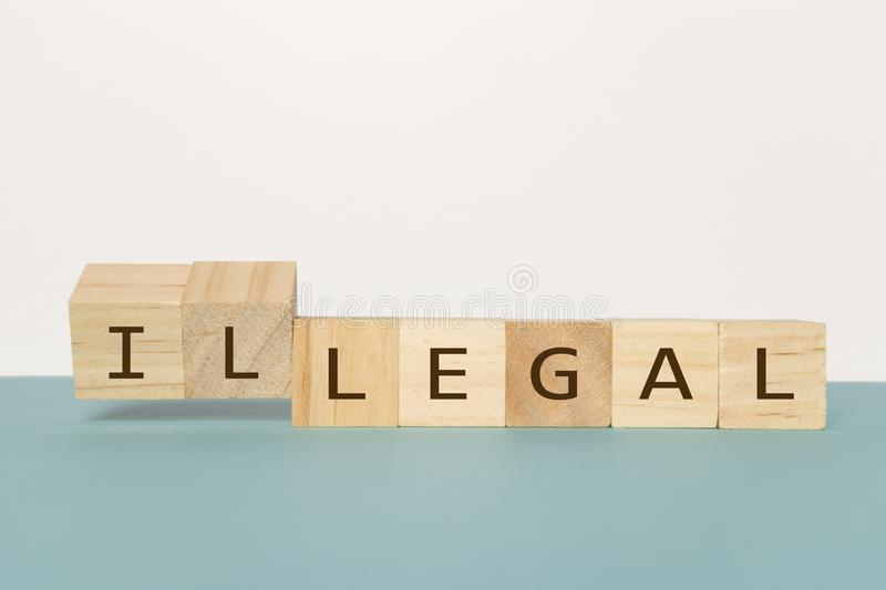 Würfel zwei leicht schlagen hölzernen, um das Wort legal zu illegalem auf neutralem Hintergrund zu ändern lizenzfreies stockbild