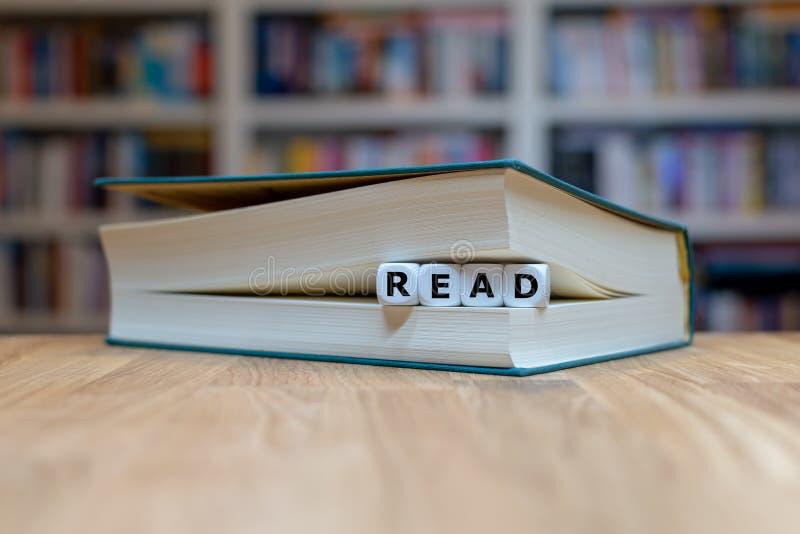 Würfeln Sie in einer Buchform das Wort 'LESEN ' lizenzfreies stockbild