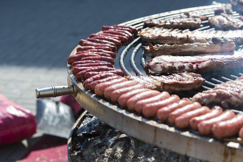 Würste und Rippe des Rindfleisches und des Schweinefleisch, die auf einem großen Bratpfanne braten lizenzfreie stockfotografie