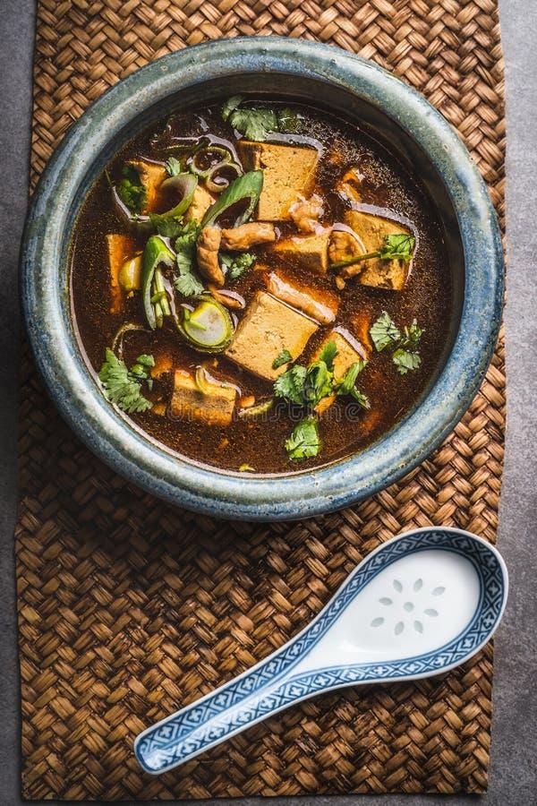 Würzige asiatische Suppe mit Tofu und Fleisch in der Schüssel, Draufsicht Sichuan-Suppe lizenzfreie stockfotos