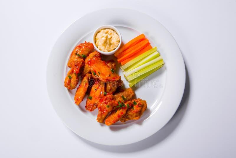 Würzige BBQ-BüffelHühnerflügel, die auf der Platte geschmückt mit Karotten- und Selleriestöcken mit Blauschimmelkäsedip sitzen stockfoto