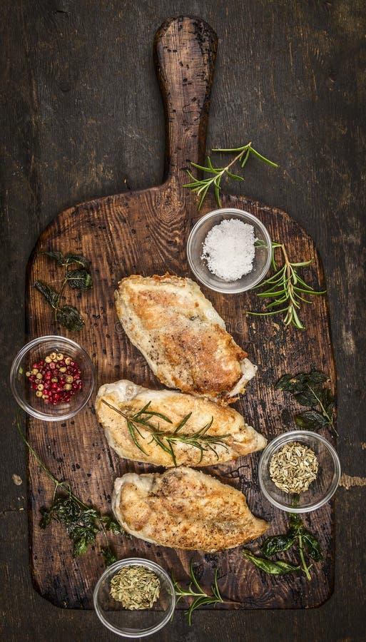 Würzige gebackene Hühnerbrust auf rustikalem hölzernem ausweidendem Brett, Draufsicht lizenzfreie stockfotos
