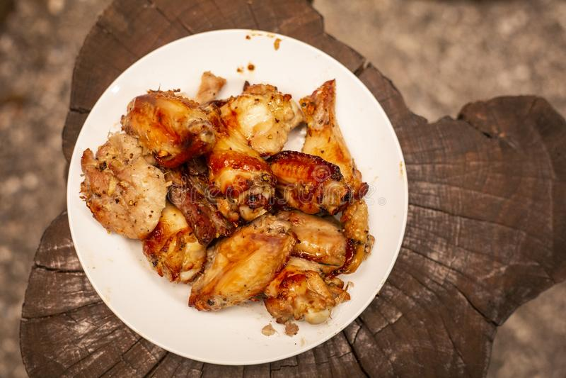 Würzige Hühnerflügel und Beine, die mit heißen Flammen grillen lizenzfreie stockbilder