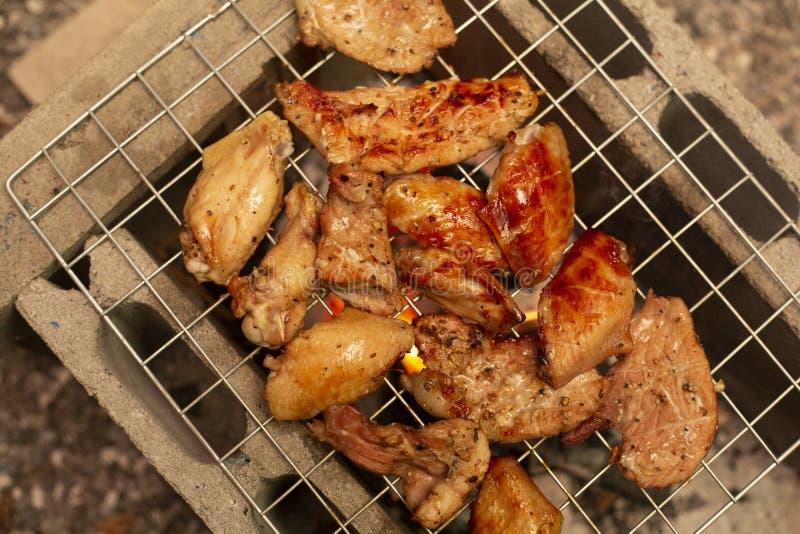Würzige Hühnerflügel und Beine, die mit heißen Flammen grillen lizenzfreies stockfoto