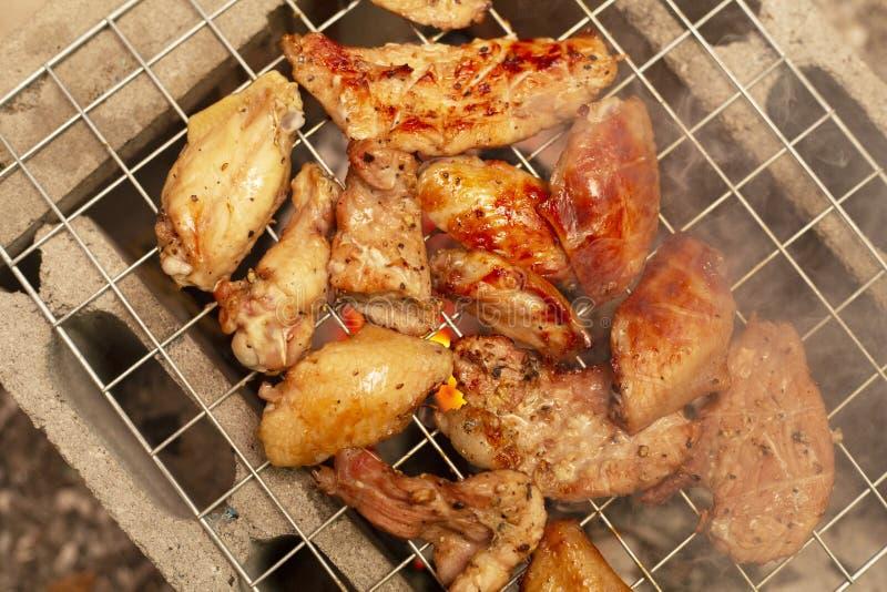 Würzige Hühnerflügel und Beine, die mit heißen Flammen grillen lizenzfreie stockfotos