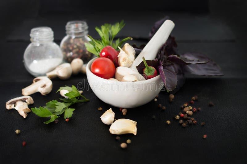 Würzige Kräuter, Knoblauch und Tomaten in einem weißen Mörser für Soße lizenzfreie stockfotografie