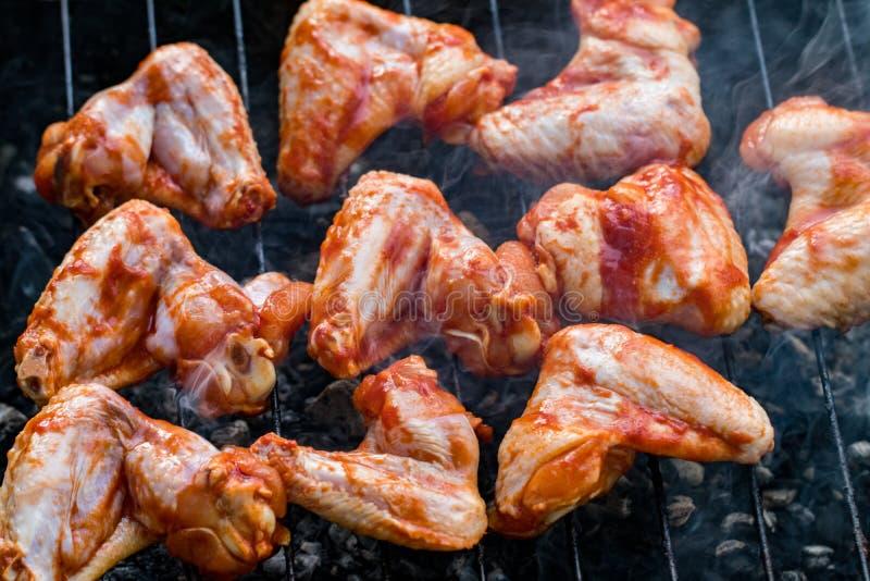 Würzige marinierte Hühnerflügel, die auf einem Sommergrill mit grillen lizenzfreies stockfoto