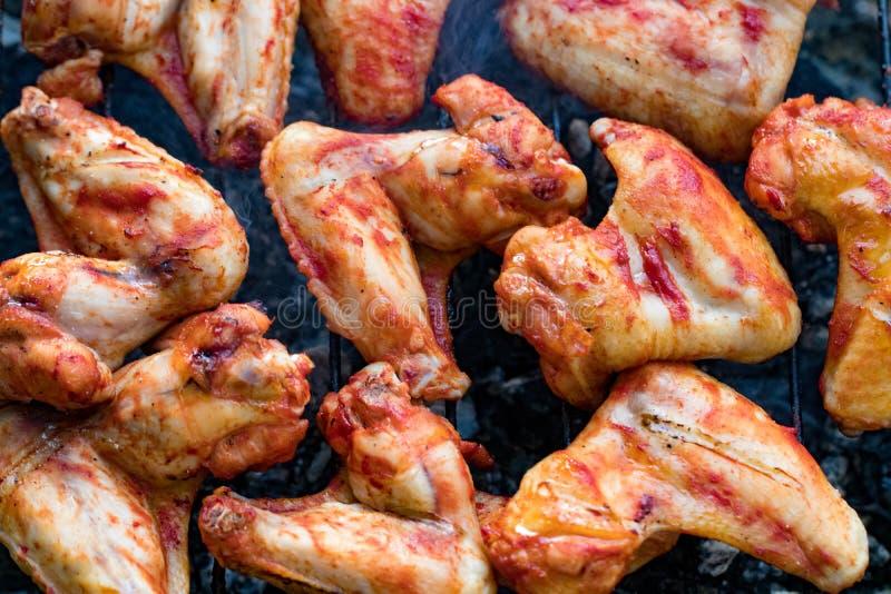 Würzige marinierte Hühnerflügel, die auf einem Sommergrill mit grillen lizenzfreie stockfotos