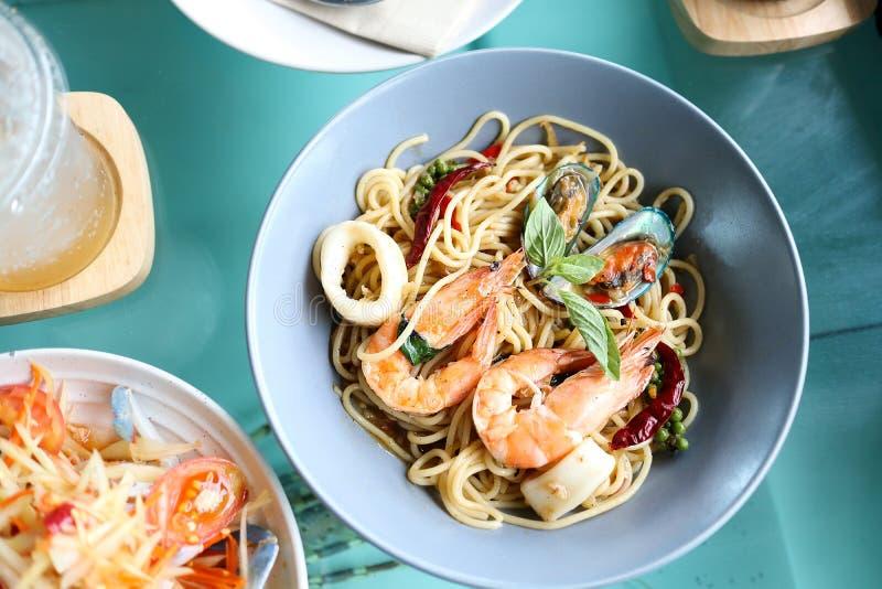 Würzige Meeresfrüchte der Spaghettis im blauen Teller auf dem Tisch stockfotografie