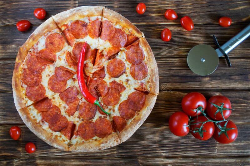W?rzige Pepperonis und Salamipizzal?gen auf einer Holzoberfl?che von Kiefernplanken nahe bei einem speziellen Rundmesser, Tomaten lizenzfreie stockfotos