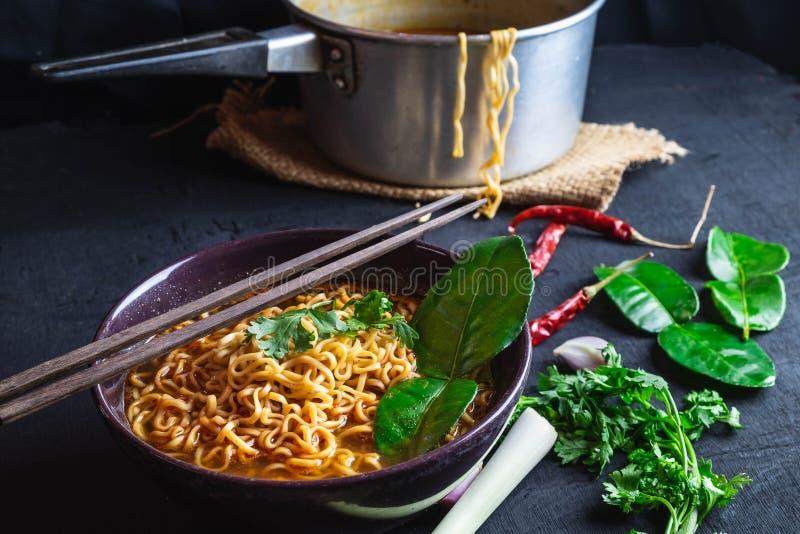 Würzige sofortige Nudelsuppe und Gemüse auf einem schwarzen Hintergrund lizenzfreies stockfoto