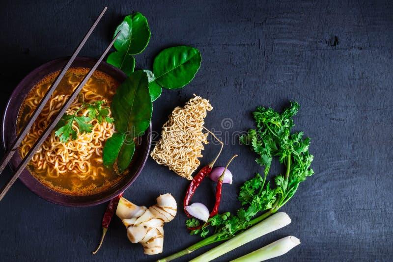 Würzige sofortige Nudelsuppe und Gemüse auf einem schwarzen Hintergrund lizenzfreie stockbilder