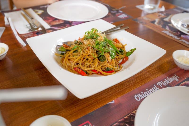Würzige Spaghettimahlzeit auf der hölzernen Tabelle lizenzfreies stockfoto