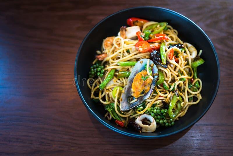 Würzige Spaghettis mit Meeresfrüchten im schwarzen Teller auf Holztisch lizenzfreies stockfoto