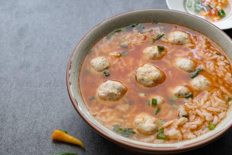 Würzige Suppe des Reises mit Hühnerball und Paprikas in der grauen Schüssel auf Tabelle lizenzfreie stockfotografie