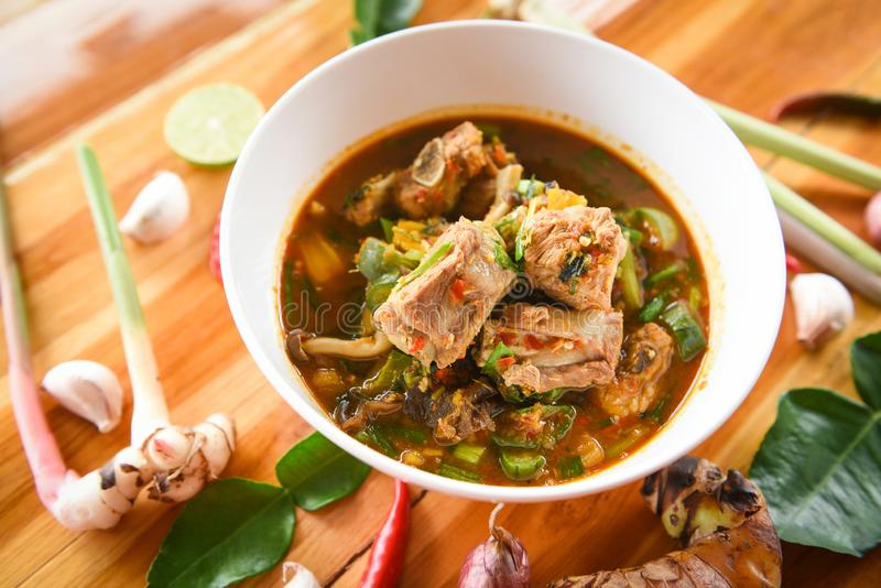 Würzige Suppe des Schweinefleischrippen-Currys/Schweinefleischknochen mit heißer und saurer Suppenschüssel mit thailändischen Krä stockbild