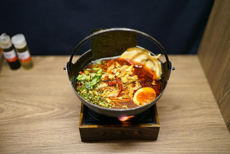 Würzige Tonkotsu-Ramen - eine Schüssel japanische Nudelsuppe gemacht vom Vorrat basiert auf der Schweinefleischknochensuppe, gemi stockbild