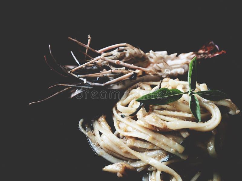 Würziger Garnele Linguine mit getrocknetem Paprika und Knoblauch auf schwarzem backg lizenzfreie stockfotos