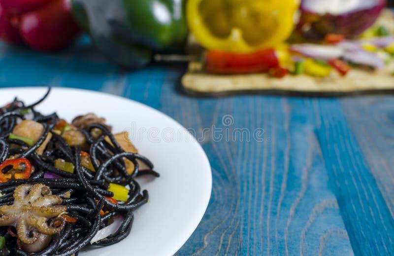 Würziger schwarzer Spaghettiteller mit Meeresfrüchten und Gemüse auf einer Seitenansicht des weißen Hintergrundes der Platte blau lizenzfreies stockbild