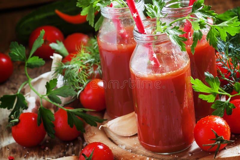 Würziger Tomatensaft in den kleinen Flaschen mit Strohen, Kirschtomaten stockfotos