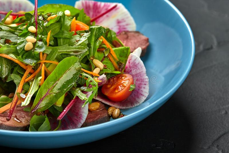 Würziges Rindfleisch schneidet Fleischsalat mit Tomaten, Petersilie, Rettich und Salat lässt Spinat in einer blauen Platte auf ei stockfoto