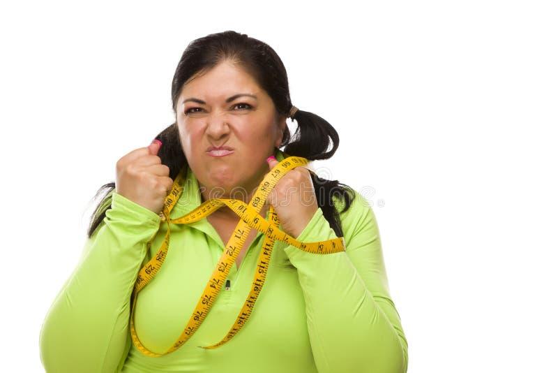 Wütende hispanische Frau oben gebunden mit Band-Maß stockbilder
