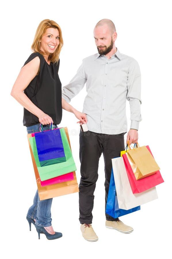 Wütender Ehemann und glückliche Frau, die Kreditkarte verwendet stockfotografie