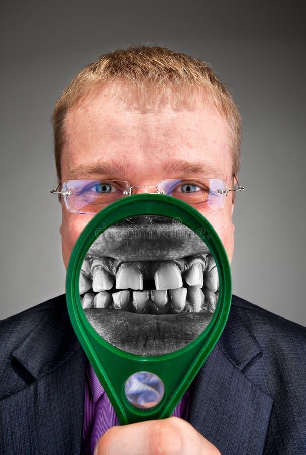 Wütender Geschäftsmann, der durch Vergrößerungsglas lächelt lizenzfreie stockbilder
