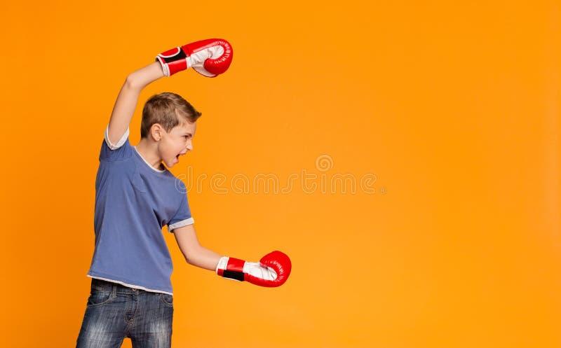 Wütender Jugendlicher in den Boxhandschuhen schreiend und angreifend lizenzfreie stockbilder