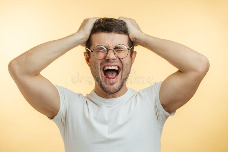 Wütender junger Mann, der am Haar zupft stockfotos