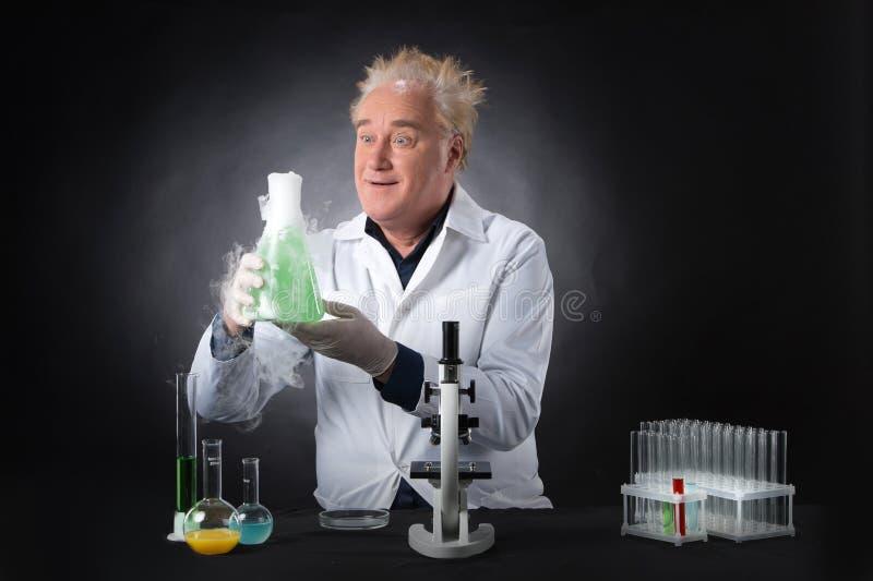 Wütender Kliniker studiert im Labor und Haltenflasche stockfotos