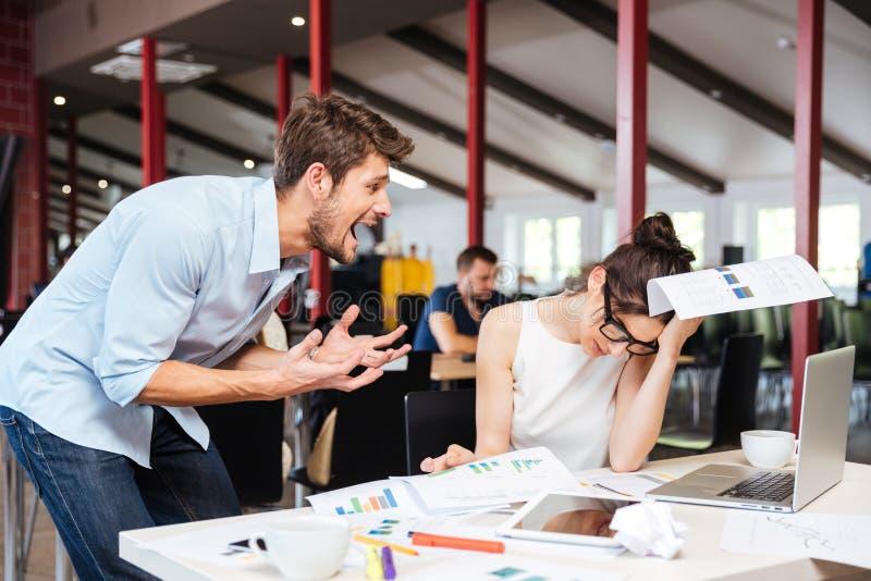 Wütender verrückter Geschäftsmann, der mit trauriger betonter Geschäftsfrau im Büro argumentiert stockfotografie