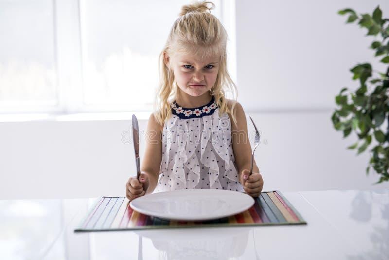 Wütendes Warteabendessen des kleinen Mädchens Halten einer Gabel in der Hand lizenzfreies stockbild