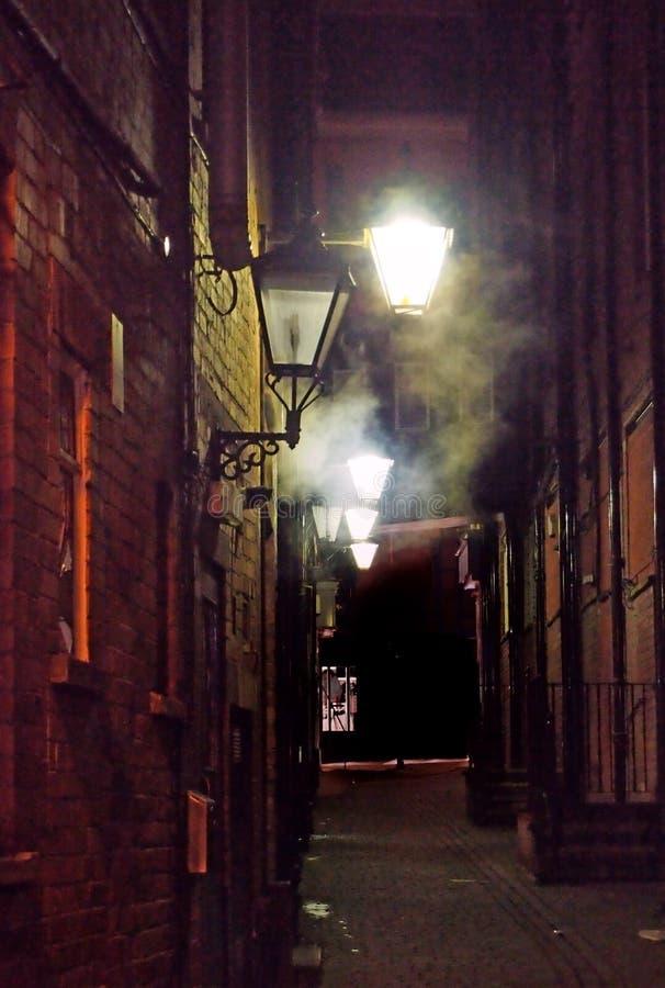 Wąska miasto aleja iluminująca starymi rozjarzonymi latarniami ulicznymi błyszczy na ścianach z cegieł z atmosferyczną wiruje mgł obrazy stock