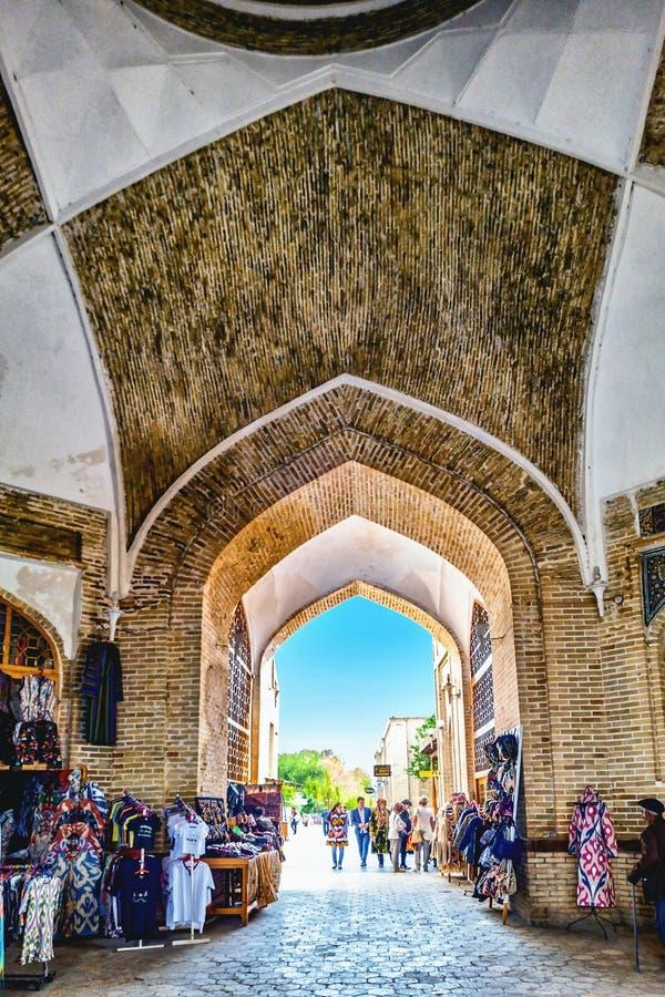 Wąska przepustka przy handlarskim kopuła rynkiem z mnogim turystą opóźnia w Bukhara, Uzbekistan fotografia stock