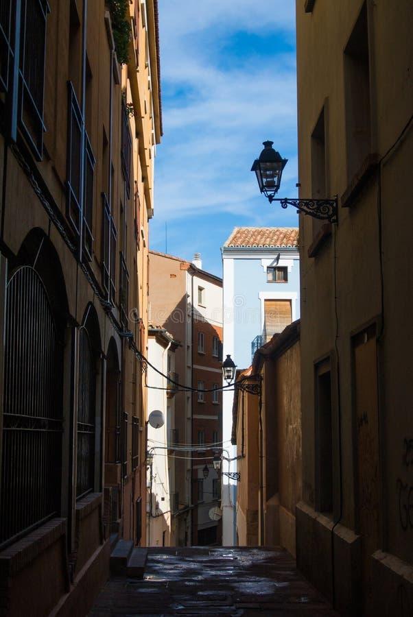 Wąska ulica z starymi domami i lampionami na ścianie przy średniowiecznym grodzkim Teruel zdjęcie royalty free