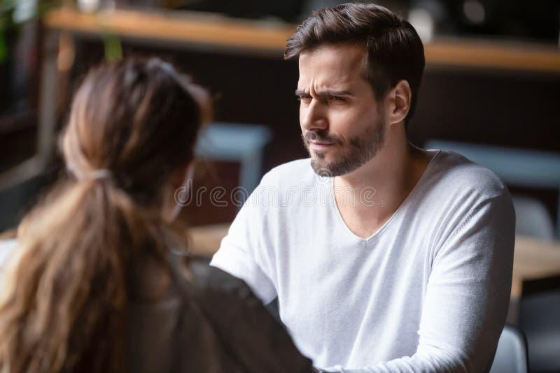 Wątpienie w niezadowolonego mężczyznę patrzącego na kobietę, zły pomysł na pierwszą randkę fotografia royalty free