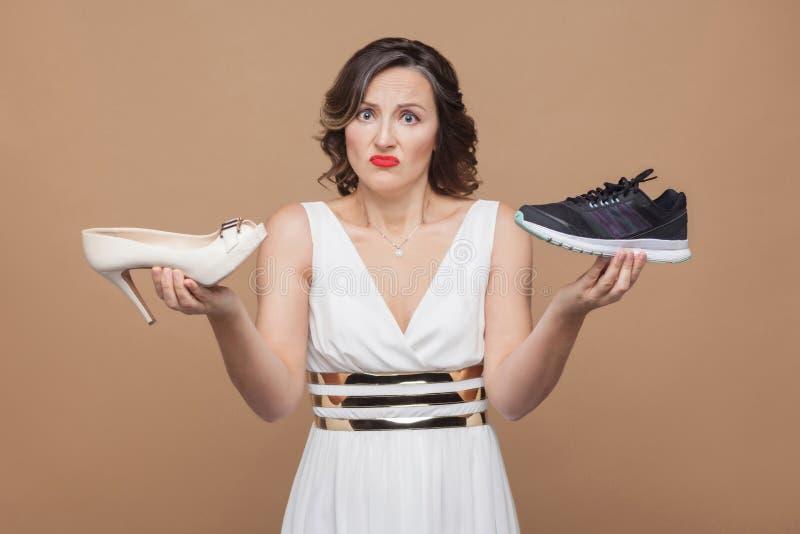 Wątpliwa myśląca biznesowa kobieta w biel sukni pozyci, holdin obraz royalty free