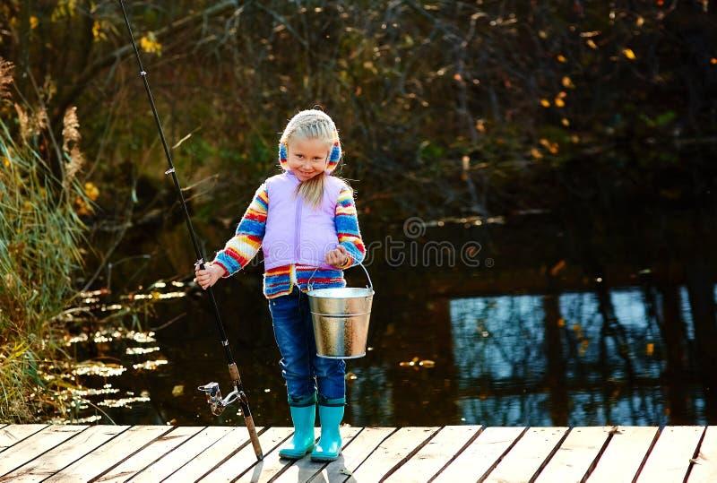 Wędkarz dziewczyna z połowu prąciem i wiadrem z chwyta stojakami na moscie obraz royalty free