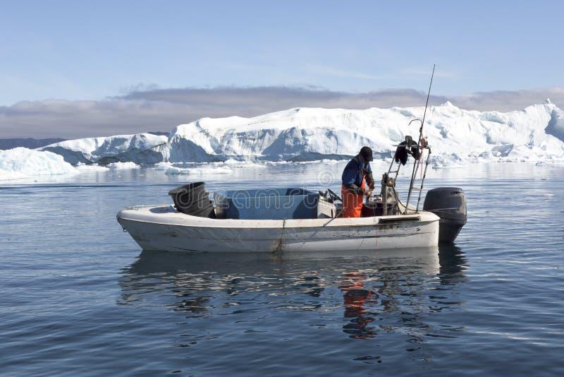 Wędkarz między górami lodowa, Greenland zdjęcie royalty free