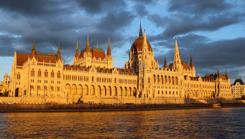 Węgierski parlamentu budynek na banku Danube rzeka wystawiająca słońca słońca ustaleni promienie z chmurnym niebem w fotografia royalty free