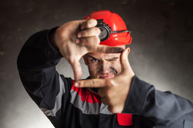 Węglowy górnik patrzeje przez palcowej ramy zdjęcia stock