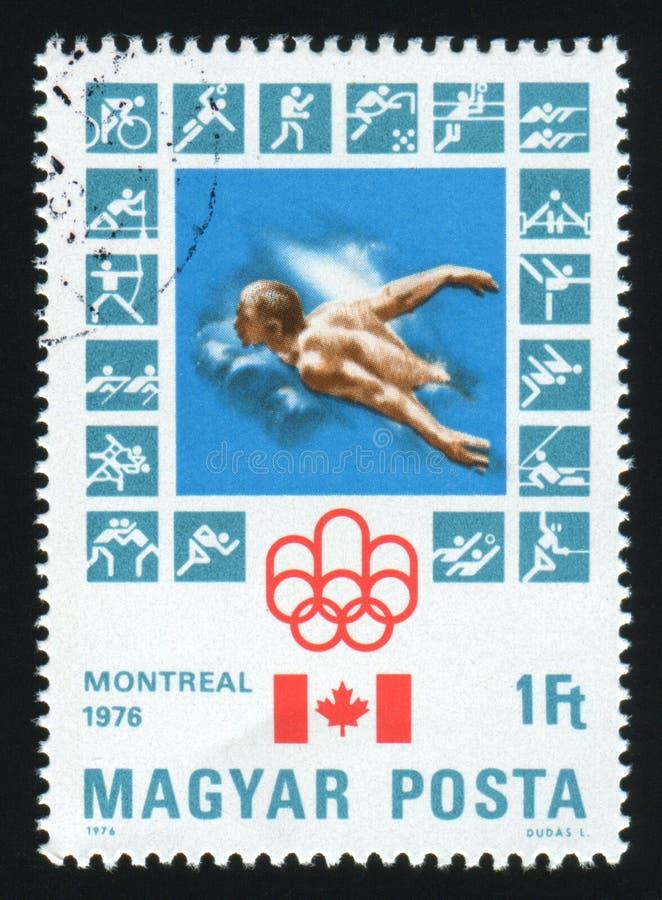 WĘGRY - OKOŁO 1976: Znaczek pocztowy drukujący Węgry, przedstawienia Montreal Olimpijski emblemat, około 1976 fotografia stock
