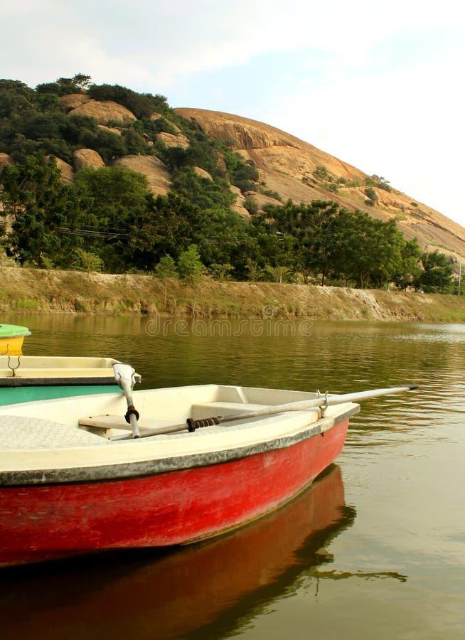 Włókno łodzie w jeziorze z wzgórzami przy sittanavasal jamy świątyni kompleksem zdjęcia stock