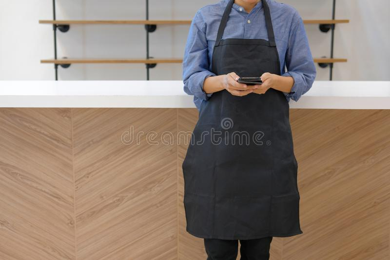 właściciel biznesu jest ubranym fartucha mienia telefon komórkowego przy kontuaru barem zdjęcie royalty free