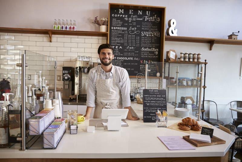 Właściciel biznesu pozycja za kontuarem przy sklep z kawą obrazy stock