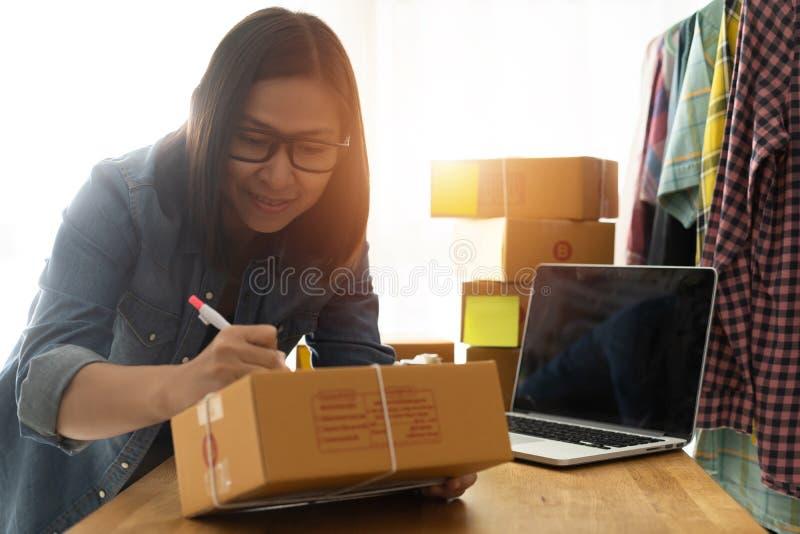 Właściciel firmy kobiety piszą adres na paczkach lub kartonach zdjęcie royalty free