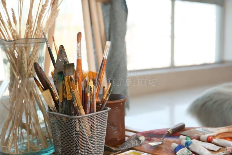 Właściciel z narzędziami i farbami na stole w artysty warsztacie obrazy stock